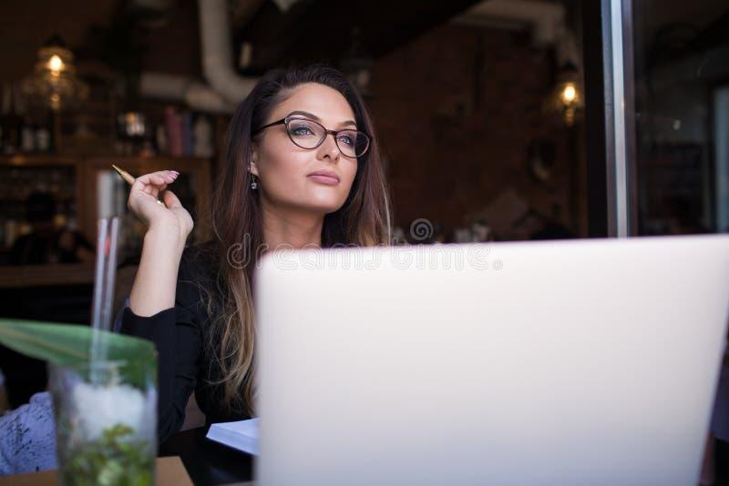 Soñando al redactor de anuncios femenino para tomar una rotura entre el trabajo en Internet vía el red-libro portátil de la PC fotos de archivo