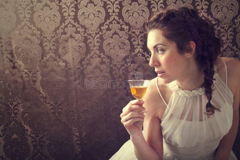 Soñando a la mujer bebe un vidrio de whisky escocés excelente fotos de archivo