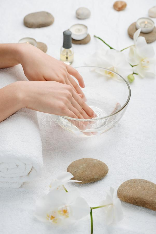 Soak nails in warm water. Before applying a manicure. Relaxation and pampering in a beauty salon stock image