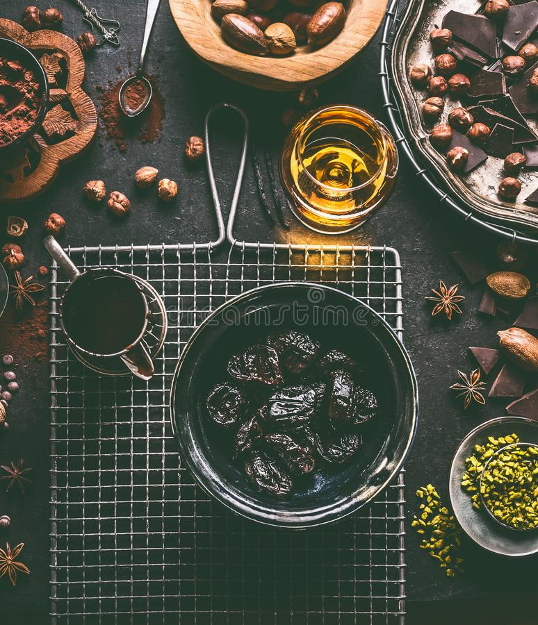 Soaked in rum prunes for homemade pralines with various chocolate, spices and nuts ingredients on dark table background stock photo