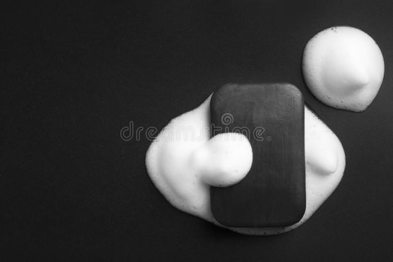 Soap bar and foam on black background, top view stock photos