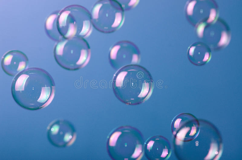 Soap bubbles on blue royalty free stock image