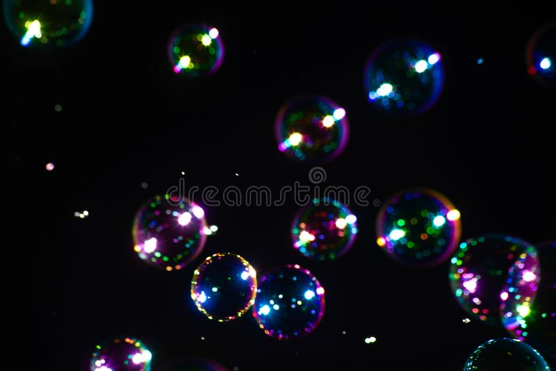 Soap bubbles on a dark background with blue, green and purple color. Bright soap bubbles on a dark background with blue, green and purple color, abstract royalty free stock photos