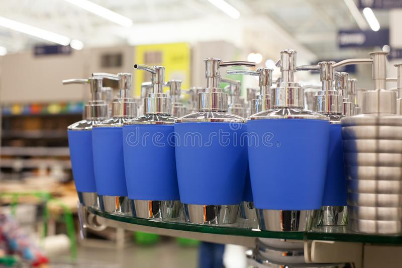 Soap dish dispenser for liquid soap, bathroom pastic and metal accessories in blue color on glass shelve in store close up, toilet stock image