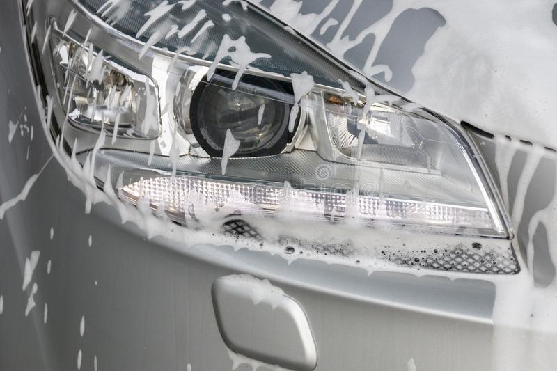 Foam On A Car Light. Soap foam on the left side of the main light of a sliver car that has its front safty light turned on royalty free stock photos