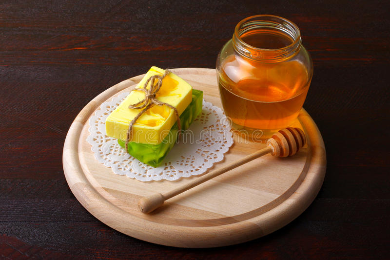 Soap and honey. Colorful natural herbal soap associated with a thread lies on the fabric on the Board for cutting with a jar of honey on wooden table royalty free stock photo