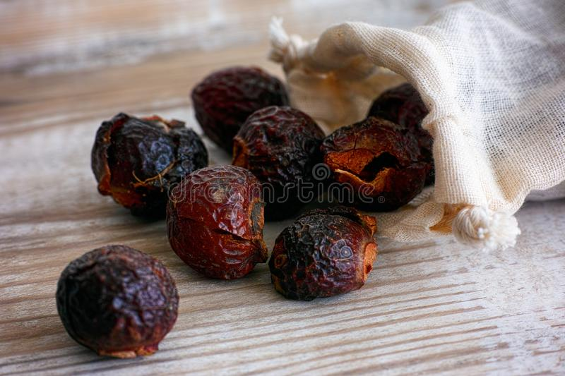 Soap nuts spilling from bag on wooden background. Close-up royalty free stock photos