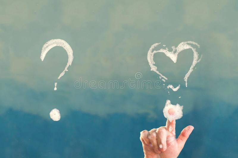 Soap question mark and shape of heart on shower cabin in the bathroom. Concept stock images