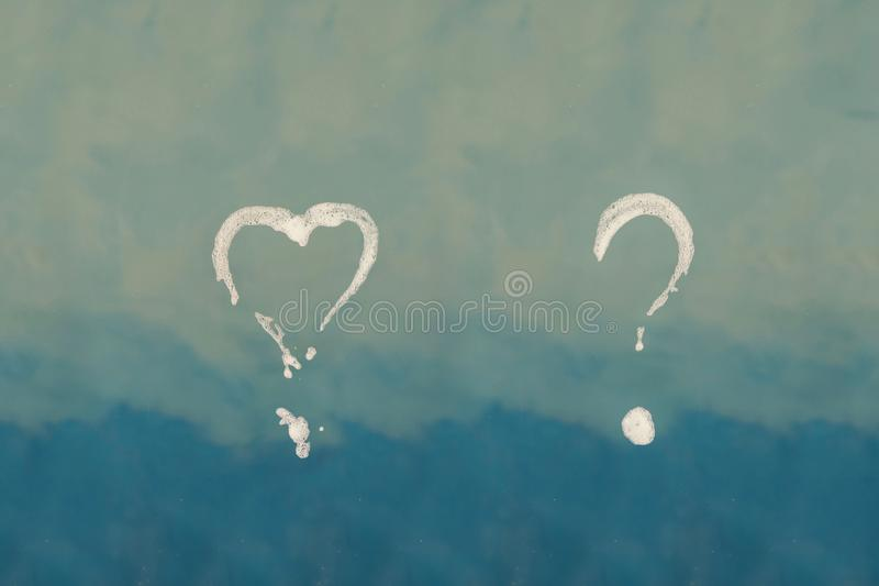 Soap question mark and shape of heart on shower cabin in the bathroom. Concept royalty free stock image