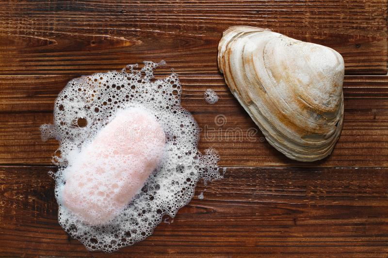 Soap And Seashell. Lathered soap bar and seashell on wood spa concept royalty free stock image