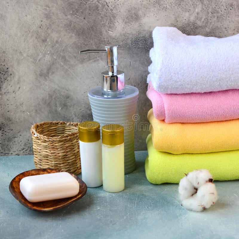 Soap, shampoo, shower gel, lotion and cotton towels on stone counter table in a bathroom. Soap, shampoo, shower gel, lotion and cotton towels on stone counter royalty free stock photos