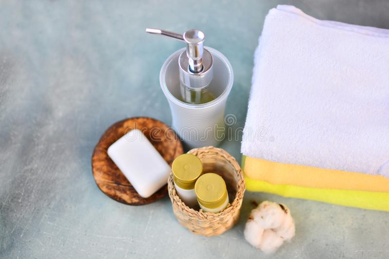 Soap, shampoo, shower gel, lotion and cotton towels on stone counter table in a bathroom. Soap, shampoo, shower gel, lotion and cotton towels on stone counter stock photography