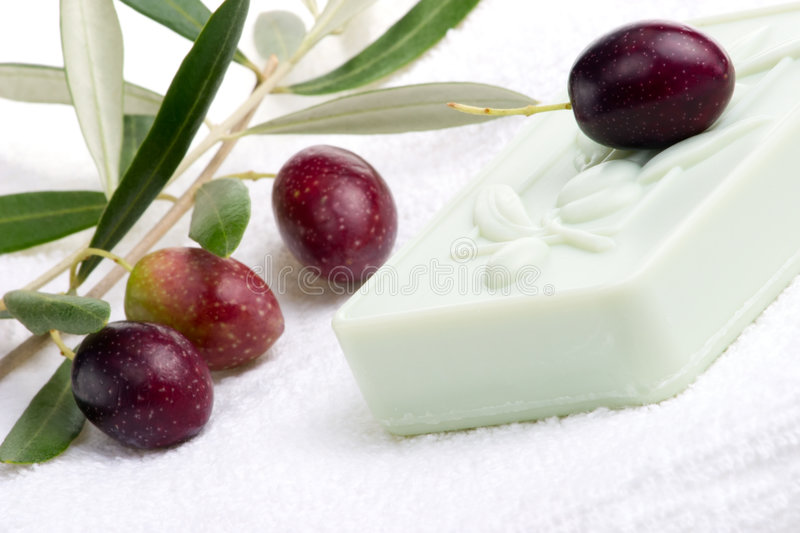 Soap spa set. Spa set - fresh black olives, oils, organic soap and towels over white towel. best suited for relaxing and health commercials stock images