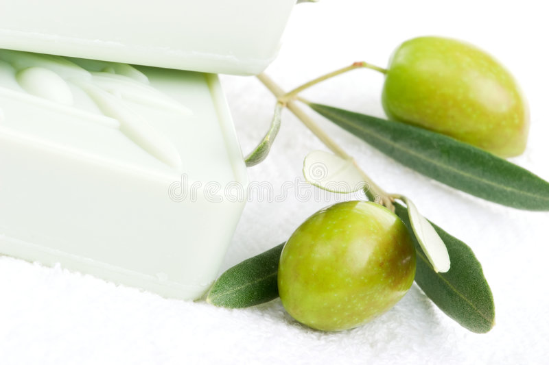 Soap spa set. Spa set - fresh green olives, oils, organic soap and towels over white towel. best suited for relaxing and health commercials royalty free stock photography