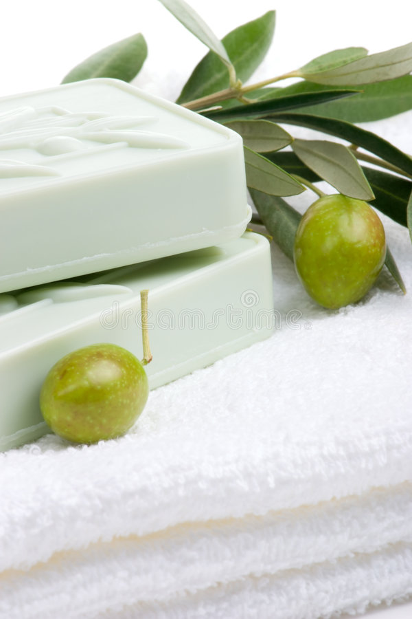 Soap spa set. Spa set - fresh green olives and organic soap over white towel. best suited for relaxing and health commercials royalty free stock image
