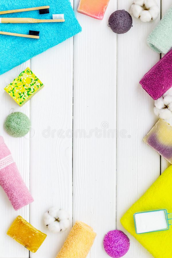 Products for laundry and wellness with cotton towels frame on white wooden background top view copy space royalty free stock photos