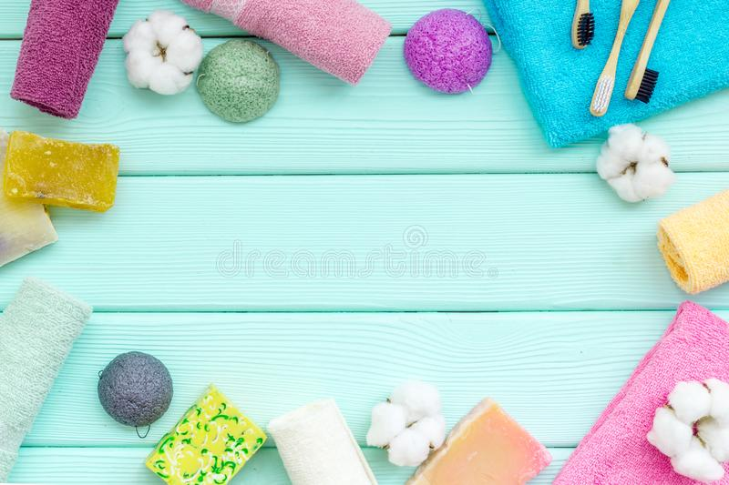 Spa or resort cosmetics and cotton towels to take bath frame on mint green wooden background top view space for text stock photos