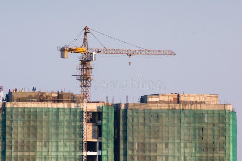 Sob a construção da construção com um guindaste em redes da parte superior e de segurança imagem de stock