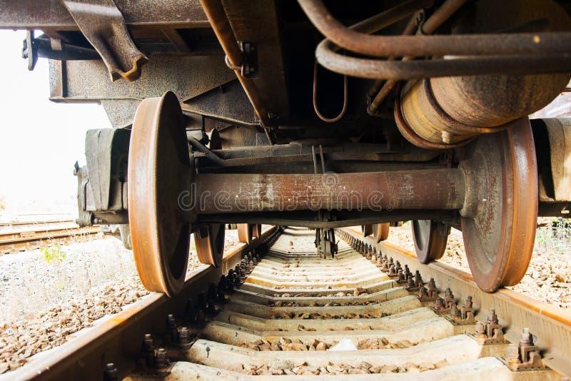 Sob de um trem de mercadorias velho nas trilhas railway Vagão oxidado imagem de stock