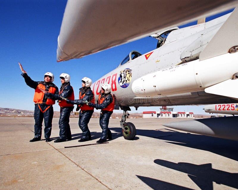 Sob o céu azul, um aeroporto militar, piloto quatro ao lado dos lutadores oito aviões migra o treinamento da simulação foto de stock