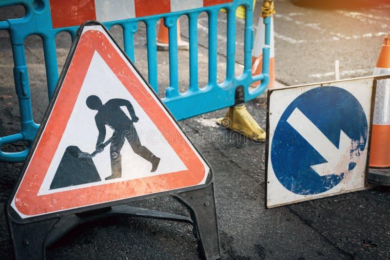 Sob o sinal da placa da construção na estrada fechado com sinal da seta e cone do tráfego fotografia de stock royalty free