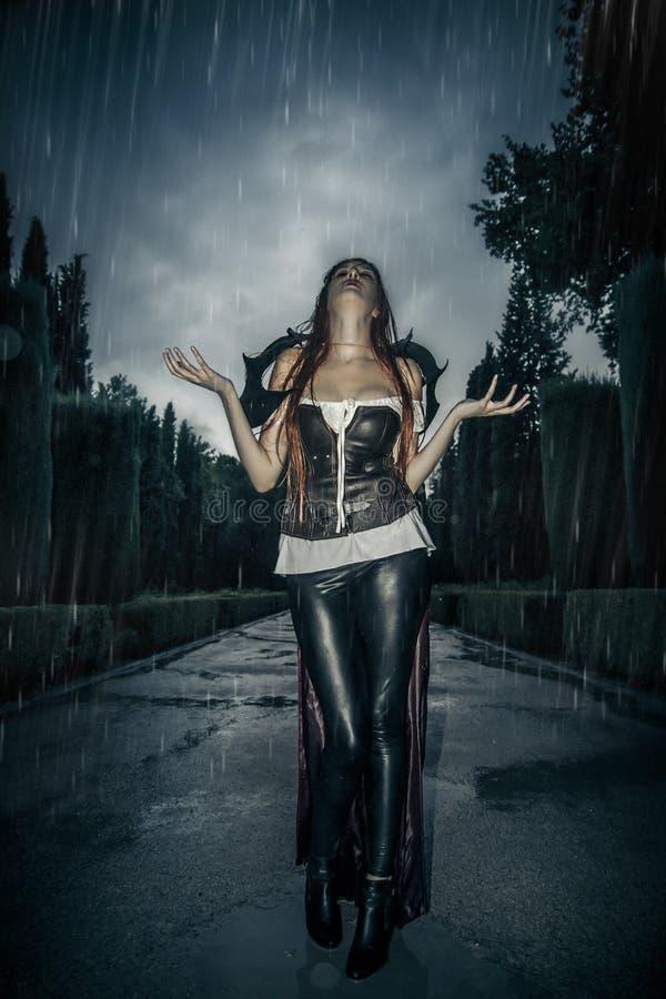 Sob a tempestade, mulher bonita do vampiro na porta do palácio, gótico fotos de stock
