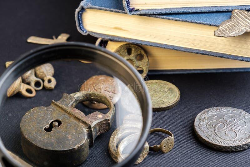 Sob uma lupa é considerada um cadeado de cobre velho em torno de uma moeda velha e de um livro, um fundo escuro de pano foto de stock royalty free