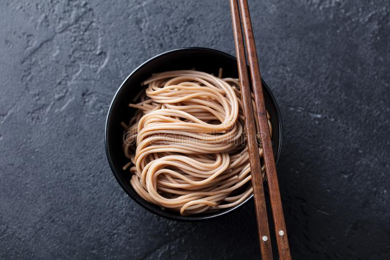 Soba noodles on a black bowl with wooden chopsticks. Slate background. Top view. royalty free stock images