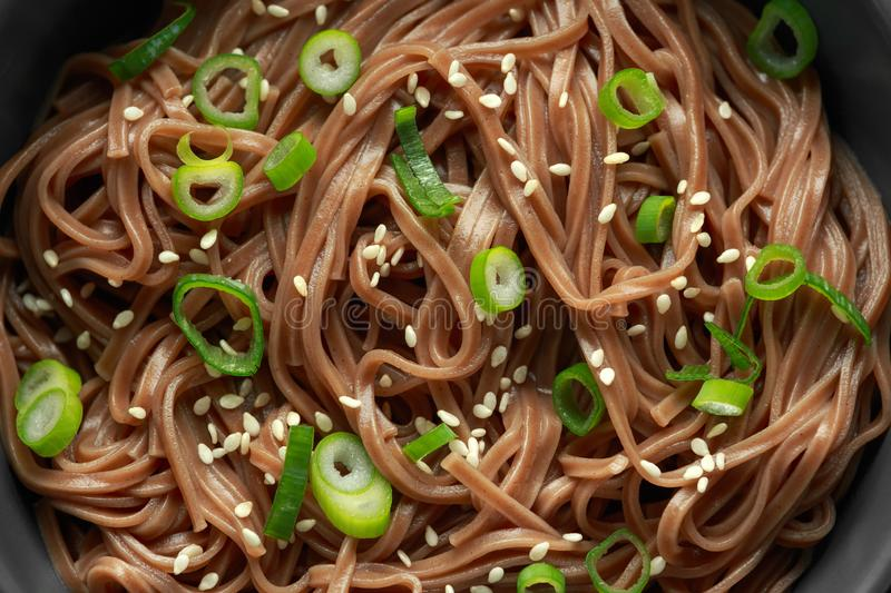 Soba noodles, buckwheat on a black bowl, with spring onion and sesame seeds. Traditional Japanese food. royalty free stock images