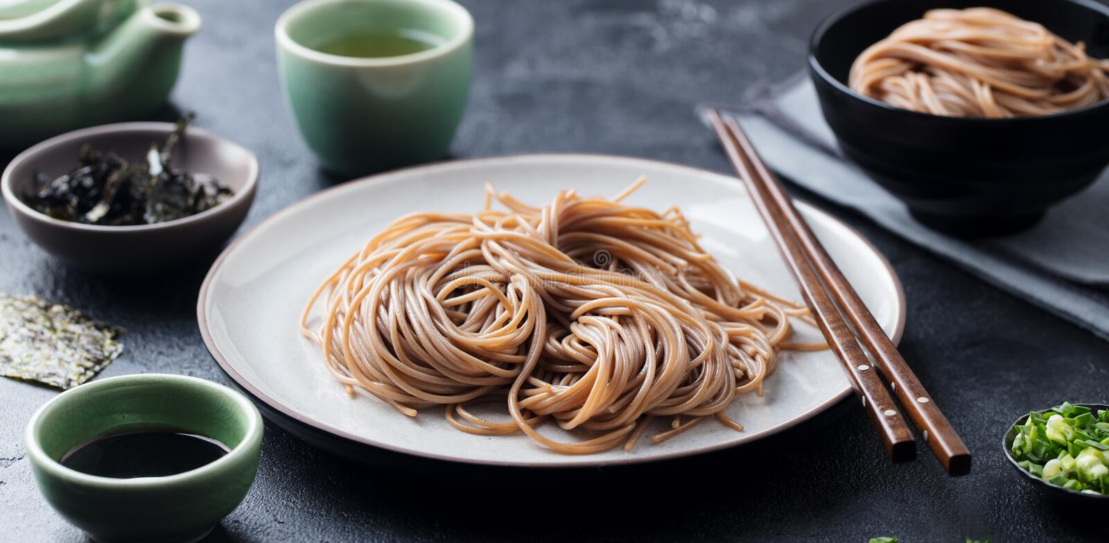 Soba noodles with sauce and green tea set. Japanese food. Black slate background. stock photography
