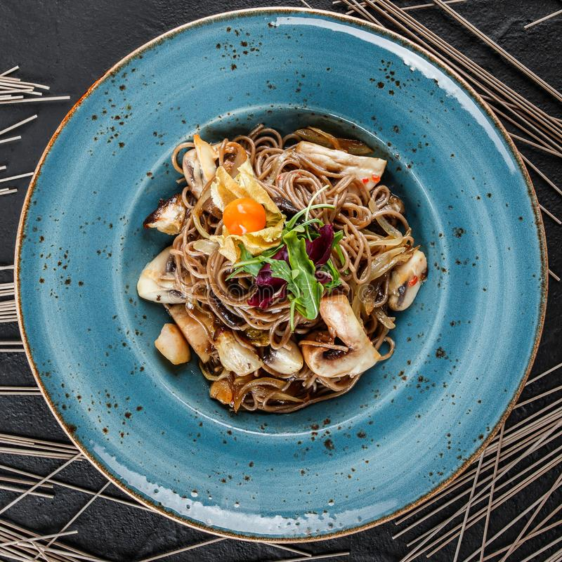 Soba noodles with wild mushrooms in sweet and sour sauce, onions and greens in plate on dark stone background. Top view.  stock photo