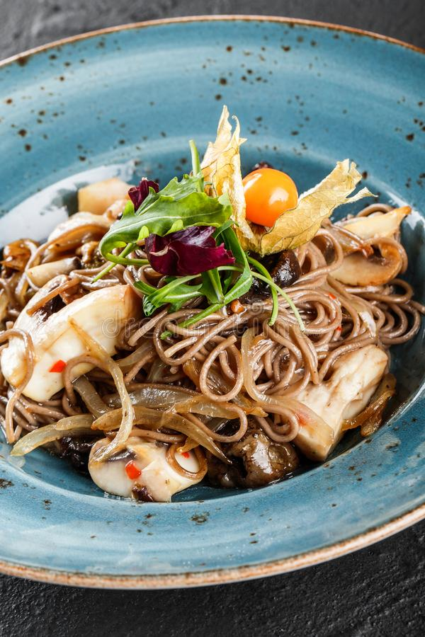 Soba noodles with wild mushrooms in sweet and sour sauce, onions and greens in plate on dark stone background. Vegetarian food.  royalty free stock photos