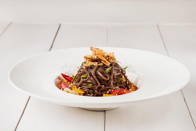 Soba-Nudeln von Buchweizen Nudeln des Buchweizens färben Pfeffer, Tomate und Kräuter gelb Pan-Asiatische Küche Platz für Text stockbilder