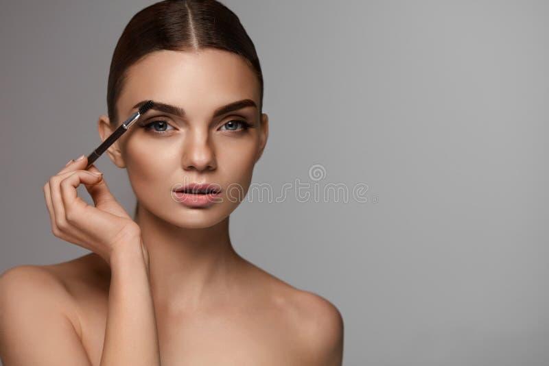 Sobrancelhas de escovadela da mulher bonita com ferramenta da testa foto de stock royalty free