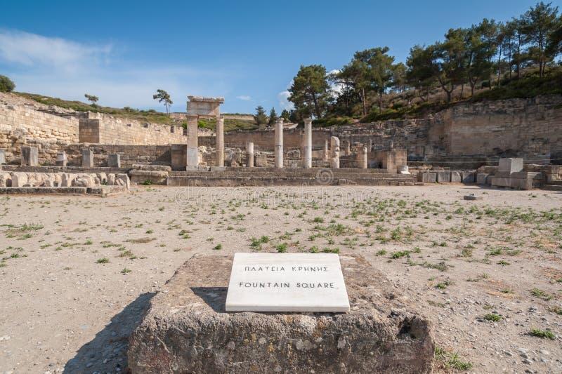 Sobras da cidade antiga de Kamiros, cidade Hellenistic mencionada pelo local Tradução: Quadrado da fonte Ilha grega do Rodes foto de stock