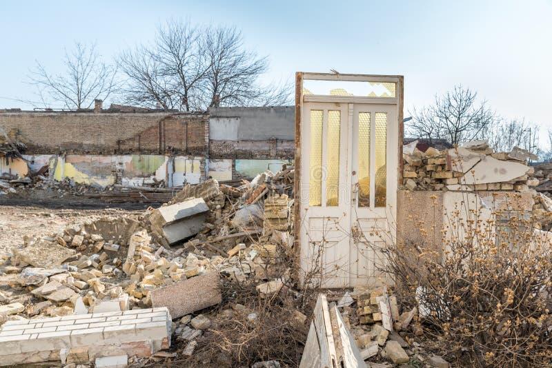 Sobras de dano do desastre das consequências do furacão ou do terremoto em casas velhas arruinadas com telhado e a parede desmoro fotografia de stock
