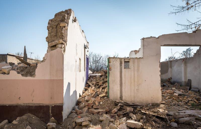Sobras de dano do desastre das consequências do furacão ou do terremoto em casas velhas arruinadas com telhado e a parede desmoro imagem de stock