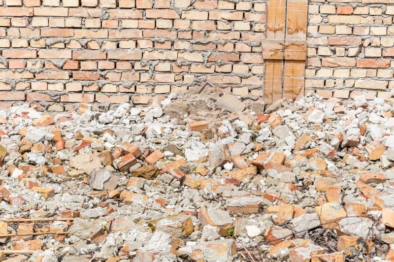 Sobras de dano do total do desastre do furacão ou do terremoto na casa ou na construção velha arruinada com a pilha dos tijolos imagens de stock royalty free
