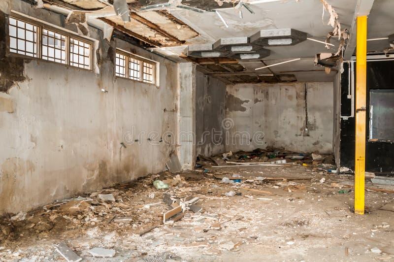 Sobras do abandonado interior danificado e destruído da casa pela granada que descasca com telhado e a parede desmoronados no sel imagens de stock