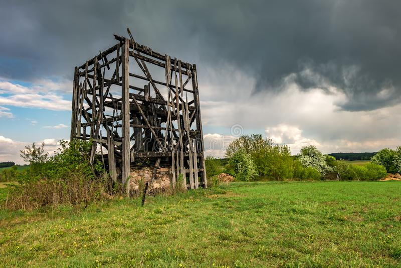 Sobras do moinho de vento queimado velho no campo antes da chuva fotos de stock