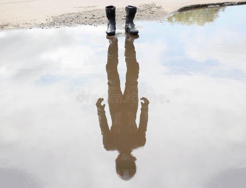 Sobre a água valha a pena sapatas do moto Na reflexão do motociclista na engrenagem imagem de stock