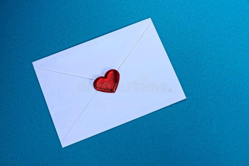 Sobre cerrado blanco con un corazón rojo en un fondo azul imagen de archivo libre de regalías
