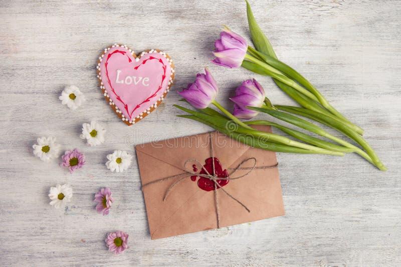 Sobre con el sello y los tulipanes de la cera en fondo de madera imágenes de archivo libres de regalías