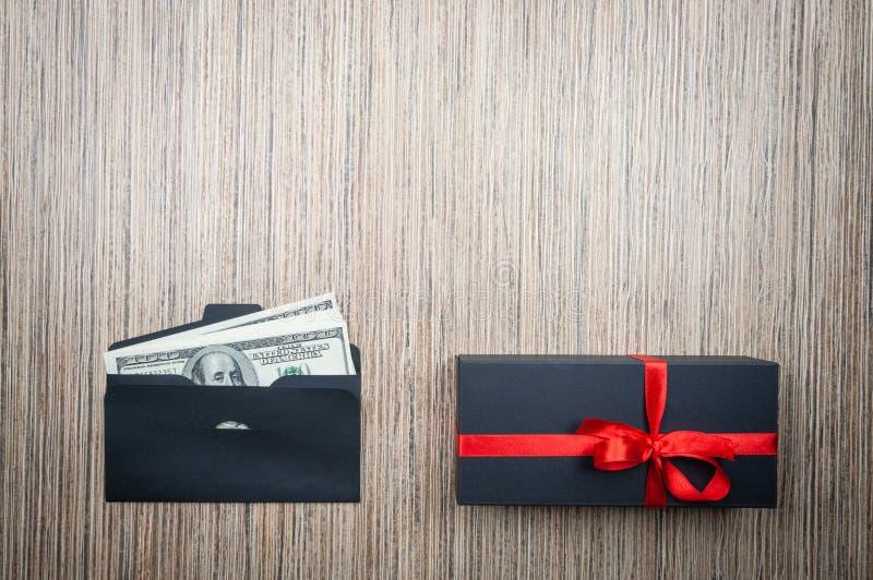 Sobre con los dólares dinero y regalo en la tabla de madera Opción difícil de la donación Copie el espacio imágenes de archivo libres de regalías