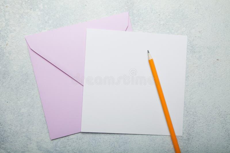 Sobre cuadrado rosado y tarjeta de felicitación en blanco en el fondo blanco del vintage fotografía de archivo libre de regalías
