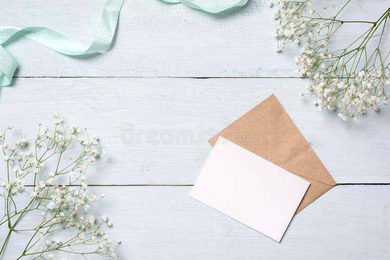 Sobre de Kraft y tarjeta en blanco en el escritorio de madera azul con las flores Tarjeta de felicitación vacía para su enhorabue imágenes de archivo libres de regalías