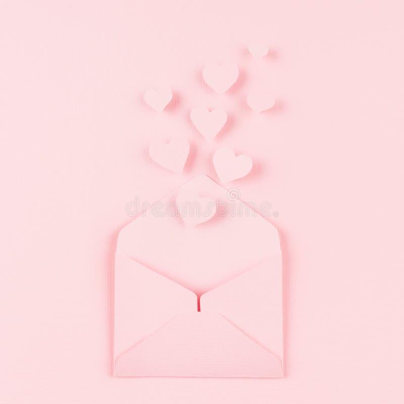 Sobre de papel abierto con los corazones de la mosca hacia fuera como mensaje del amor en fondo rosado suave del color Concepto d fotos de archivo libres de regalías