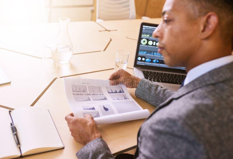 Sobre la imagen del hombro del hombre de negocios que lleva a cabo el documento con los gráficos fotografía de archivo libre de regalías