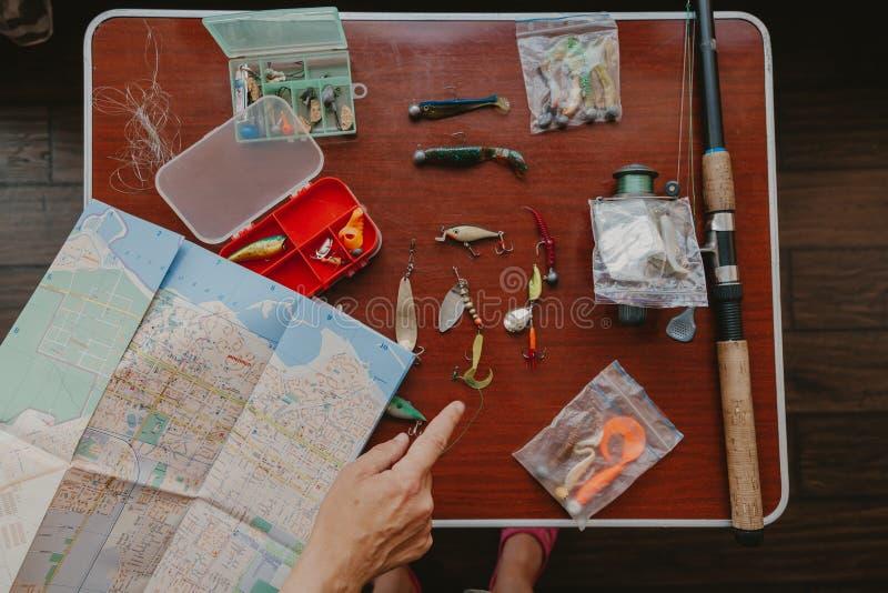 Sobre la mesa hay cebos artificiales para la pesca de lucio foto de archivo