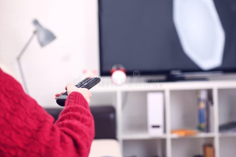 Sobre la opinión del hombro la muchacha que se sienta en el sofá que sostiene el telecontrol de la TV y que practica surf program imagen de archivo